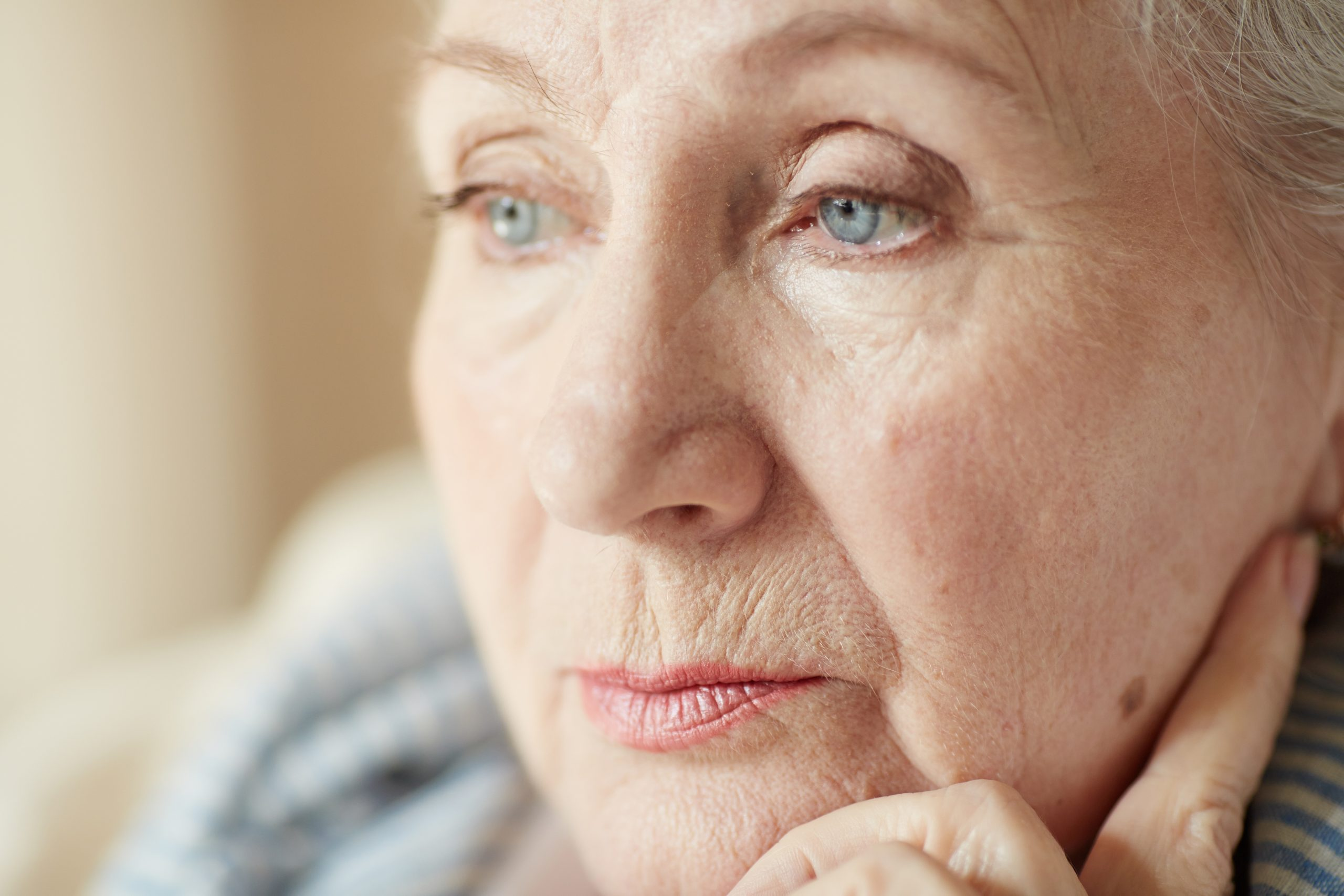 Extreme close-up shot of wrinkled retired woman with light make-up looking away pensively